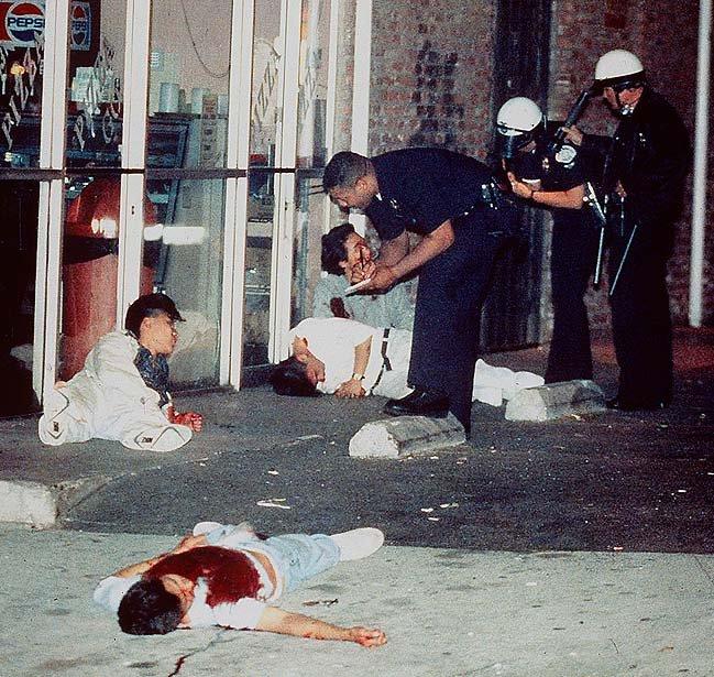 Полицейский допрашивает раненого корейца, убившего трёх цветных налётчиков