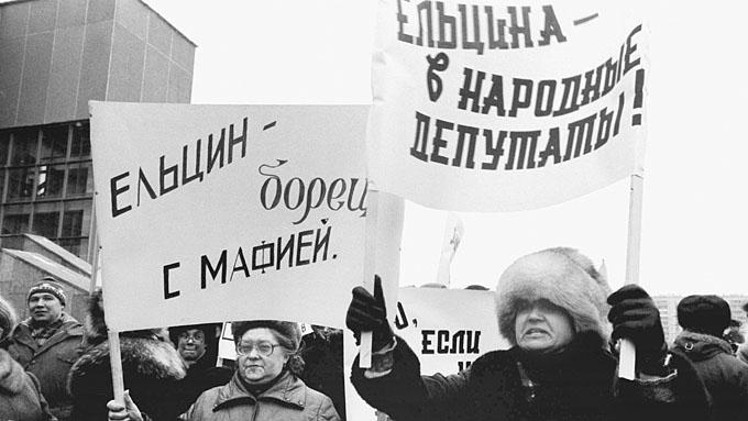 """ITAR-TASS: USSR, MOSCOW. People holding banners """"Yeltsin  - the horror of mafia"""", """"Yeltsin to beelected people's deputy"""" at the rally ahead of people's deputies of USSR pre-election meeting. (Photo ITAR-TASS/ Anatoly Morkovkin and Andrei Solovyev) Ìîñêâà. 1989 ãîäó íà îêðóæíîì ïðåäâûáîðíîì ñîáðàíèè ïî âûäâèæåíèþ êàíäèäàòîâ â íàðîäíûå äåïóòàòû ÑÑÑÐ ïî òåððèòîðèàëüíîìó èçáèðàòåëüíîìó îêðóãó ¹13 Êóíöåâñêîãî ðàéîíà ãîðîäà Ìîñêâû áûëè èçáðàíû êàíäèäàòàìè â íàðîäíûå äåïóòàòû Á. Áîíäàðåâ - ïåðâûé çàìåñòèòåëü ãåíåðàëüíîãî äèðåêòîðà íàó÷íî-ïðîèçâîäñòâåííîãî îáúåäèíåíèÿ """"Âèëñ"""", Áîðèñ Åëüöèí - ïåðâûé çàìåñòèòåëü ïðåäñåäàòåëÿ Ãîññòðîÿ ÑÑÑÐ è Â. Ðîìàøêèí - ãàçîýëåêòðîñâàðùèê çàâîäà """"Ýëåêòðîùèò"""". Íà ñíèìêå: ìèòèíã ïåðåä íà÷àëîì ñîáðàíèÿ. Ôîòî Àíàòîëèÿ Ìîðêîâêèíà è Àíäðåÿ Ñîëîâüåâà /Ôîòîõðîíèêà ÒÀÑÑ/."""