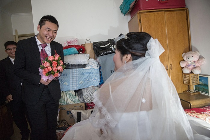 Beijing/China/story by Louisa Lim / pictures by Sim Chi Yin for NPR/  Groom Derek Wei (second from right) finally makes it through the wedding games and finds his bride Lucy Wang on the bed in her bedroom, all made-up and waiting for him.